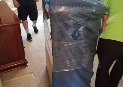 Casey and Ian wrapping an armoire